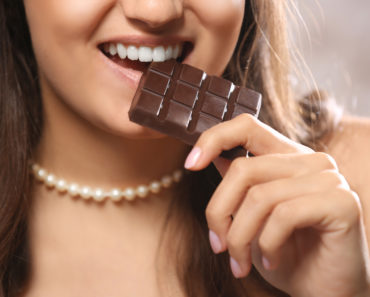 Loving chocolate woman bites bar to enjoy the taste, close up